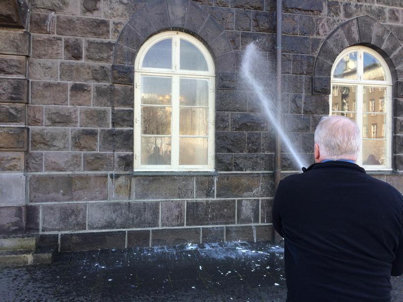 Þingvörður skolar skyrið af Alþingishúsinu.