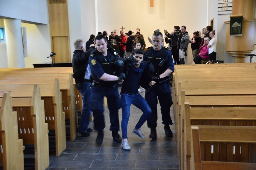 The men being dragged out of church by police.