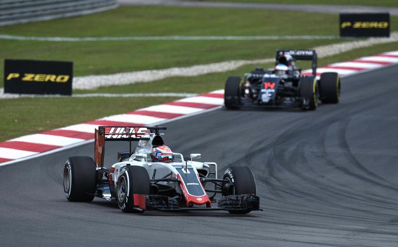 Romain Grosjean (framar) varðist Fernando Alonso hjá McLaren á fyrstu ...