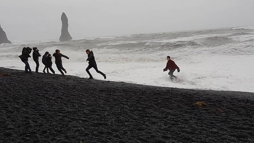 Tourists running into the waves and laughing at Iceland's most …
