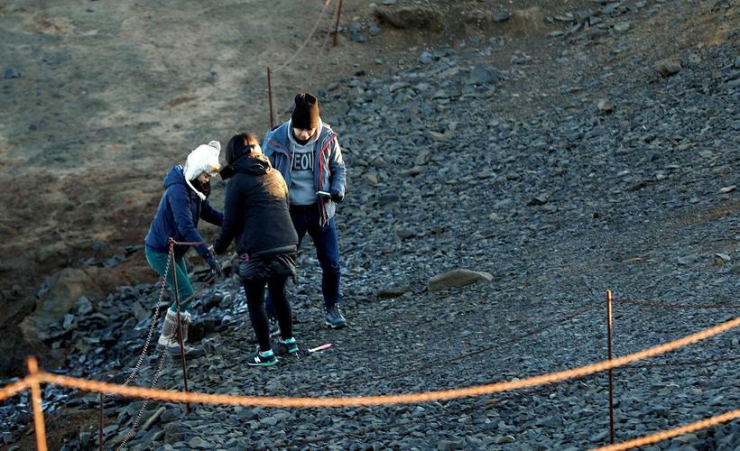 Tourists crossing barriers at Kirkjufjara.