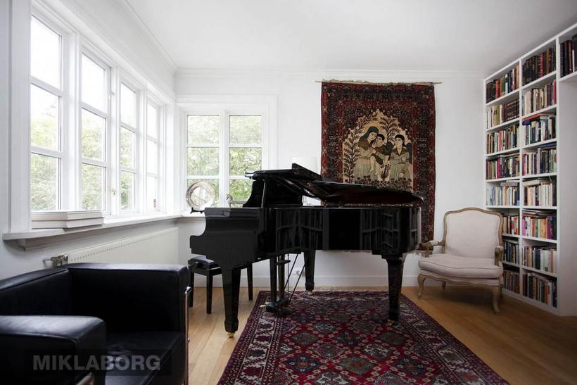 The living room features wall-to-wall books and a grand piano.