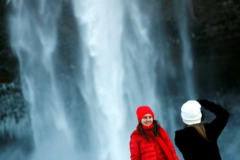 Tourists at the famous Seljalandsfoss waterfall.