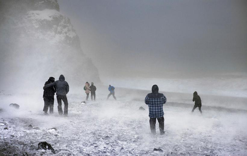 Veðurbarðir ferðamenn í Reynisfjöru. Ferðamenn virða oft að vettugi viðvaranir ...
