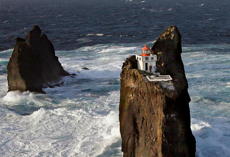 The lighthouse is surrounded by open water and is precariously …