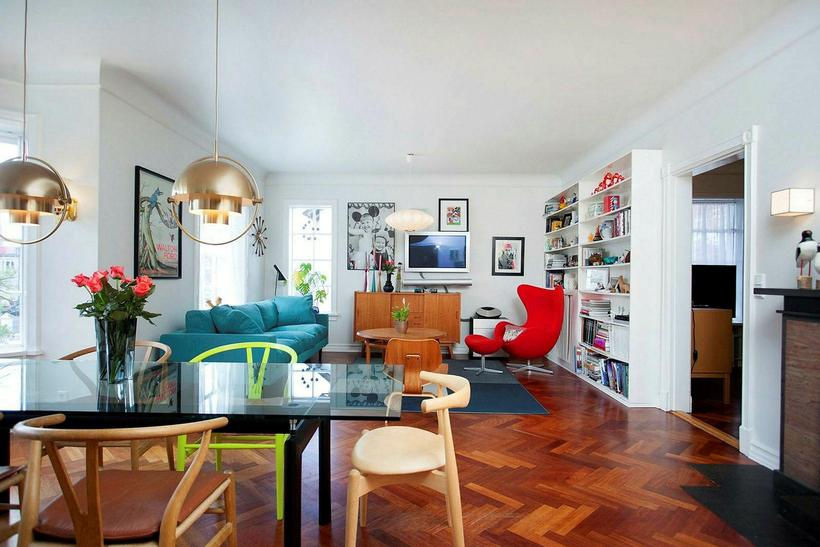 The living and dining room features a fishbone wooden floor, …