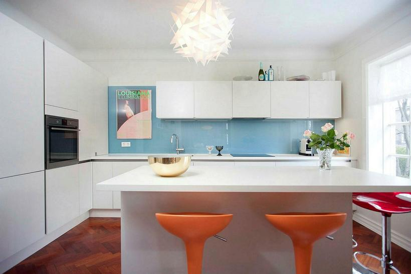 The kitchen, with blue walls and bright orange bar stools.