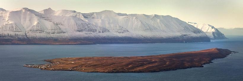 The fjord around Hrísey Island is rammed by tall mountains.