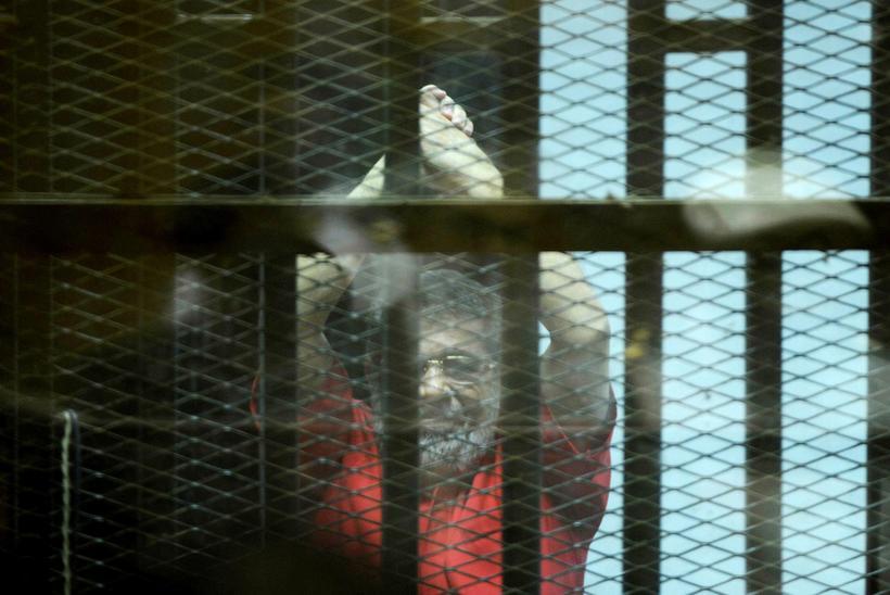 Mohamed Morsi, fyrrverandi forseti Egyptalands bak við rimlanna í réttarsalnum ...